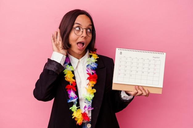 Jonge gemengde ras bedrijfsvrouw die de dagen tellen voor vakanties die op roze muur worden geïsoleerd die proberen om een roddel te luisteren
