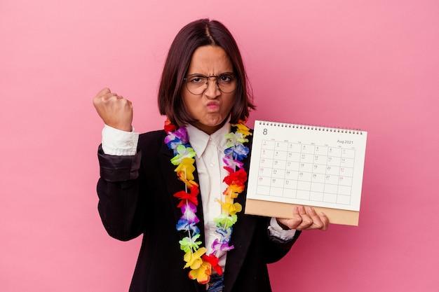 Jonge gemengde ras bedrijfsvrouw die de dagen telt voor vakanties die op roze muur worden geïsoleerd die vuist aan voorzijde, agressieve gezichtsuitdrukking toont