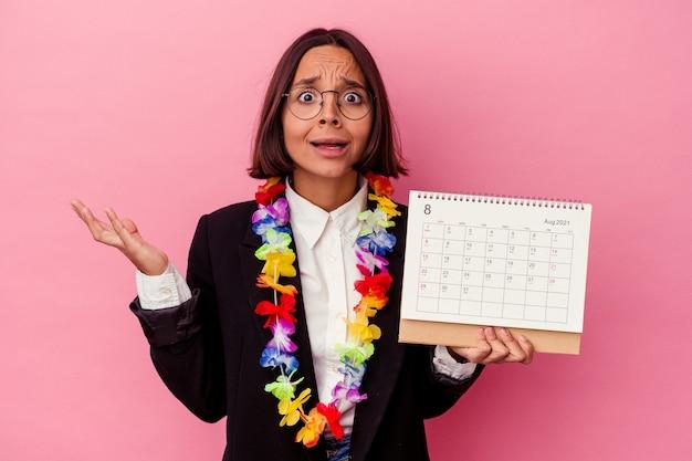 Jonge gemengde ras bedrijfsvrouw die de dagen telt voor vakanties die op roze verrast en geschokt muur worden geïsoleerd