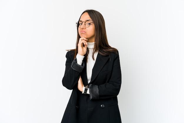 Jonge gemengde ras bedrijfsvrouw die op witte muur verdacht, onzeker wordt geïsoleerd, die u onderzoekt.