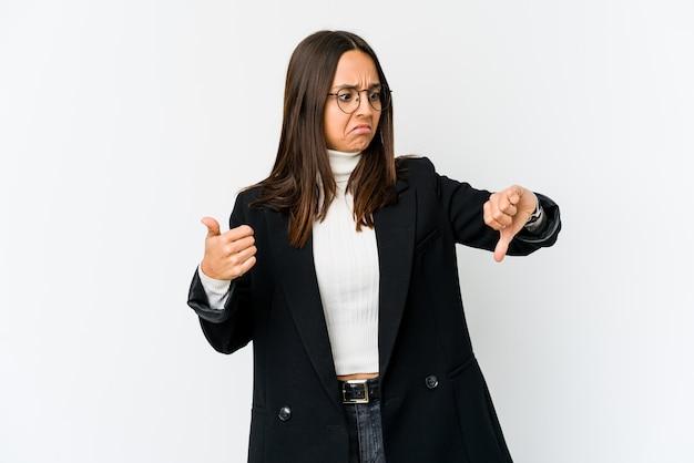 Jonge gemengde ras bedrijfsvrouw die op witte muur wordt geïsoleerd die duimen omhoog en duimen omlaag toont, moeilijk kiest concept
