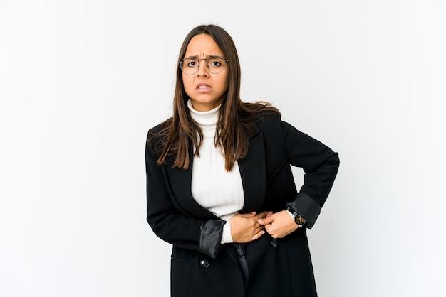 Jonge gemengde ras bedrijfsvrouw die op witte muur wordt geïsoleerd die een leverpijn, buikpijn heeft.