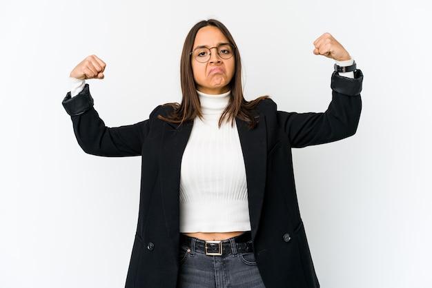 Jonge gemengde ras bedrijfsvrouw die op witte muur wordt geïsoleerd die sterktegebaar met wapens, symbool van vrouwelijke macht toont