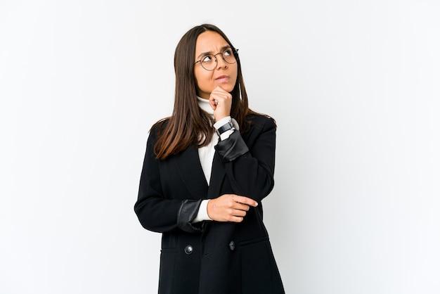 Jonge gemengde ras bedrijfsvrouw die op witte ruimte wordt geïsoleerd die zijwaarts met twijfelachtige en sceptische uitdrukking kijkt.