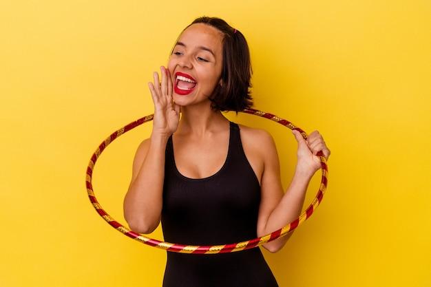 Jonge gemengde ras gymnastische vrouw die op gele muur wordt geïsoleerd die en palm dichtbij geopende mond houdt houdt