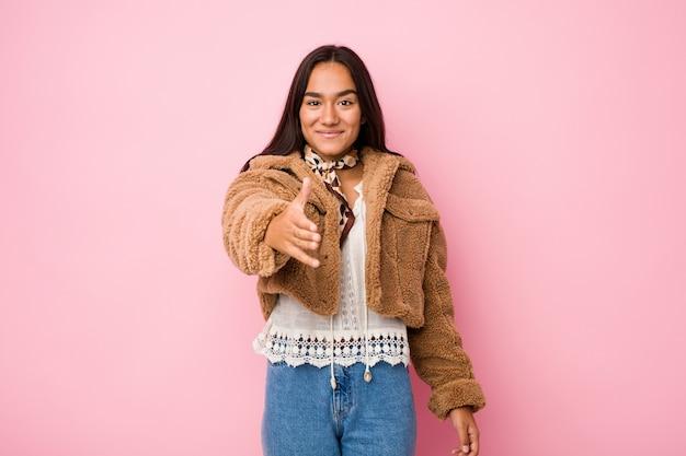 Jonge gemengde ras indische vrouw die een korte schapehuid coatstretching hand draagt bij camera in groetgebaar.