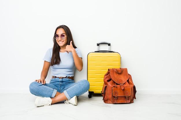 Jonge gemengde ras indische vrouw klaar om te gaan reizen tonend een mobiel telefoongesprekgebaar met vingers.