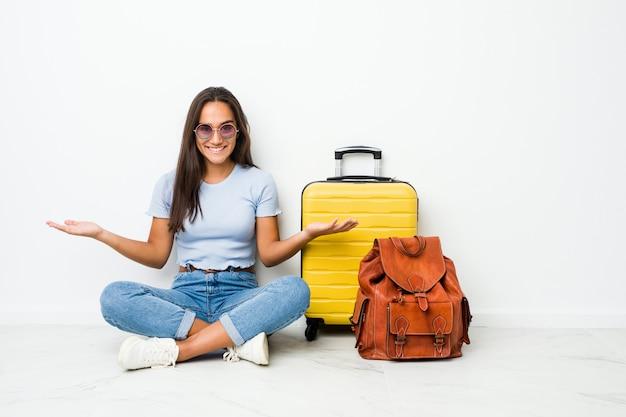 Jonge gemengde ras indische vrouw klaar om te gaan reizen tonend een welkome uitdrukking.