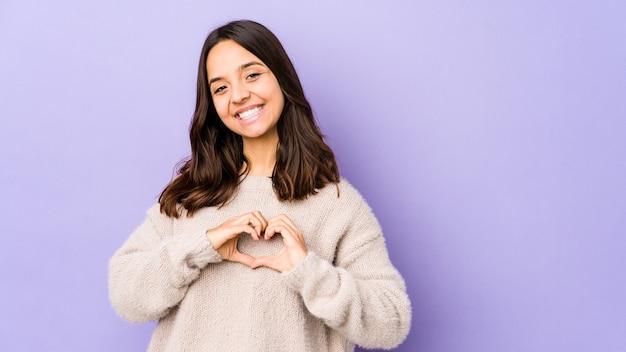 Jonge gemengde ras spaanse vrouw die en een hartvorm met handen glimlacht toont.
