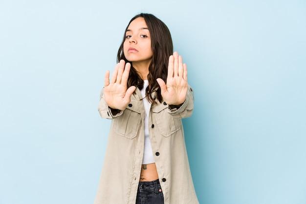 Jonge gemengde ras spaanse vrouw geïsoleerde status met uitgestrekte hand die stopbord toont, dat u verhindert.