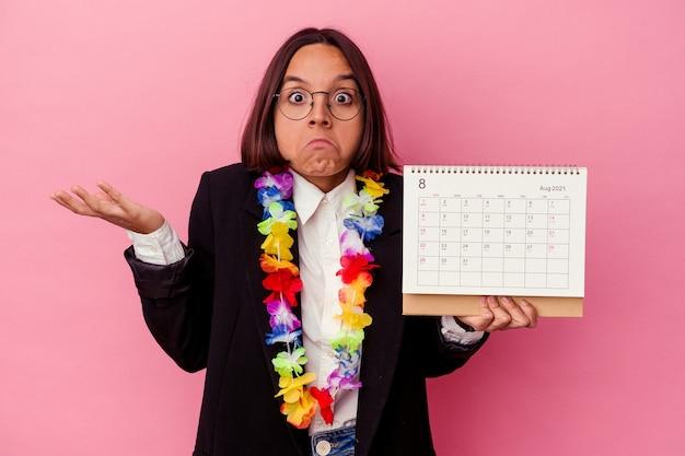 Jonge gemengde ras zakenvrouw die de dagen telt voor vakanties geïsoleerd op roze muur haalt schouders op en opent verwarde ogen