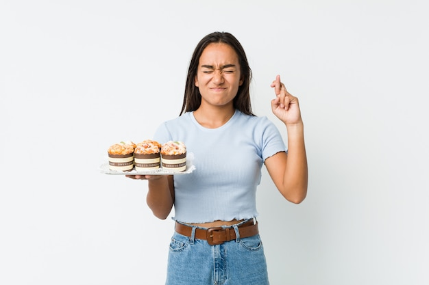 Jonge gemengde rasindiaan die zoete cakes houden die vingers kruisen voor het hebben van geluk