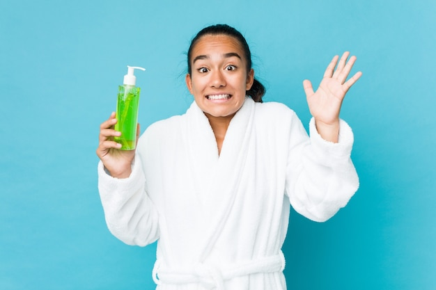 Jonge gemengde rasindiër die een fles van aloëvera houdt die een overwinning of een succes viert