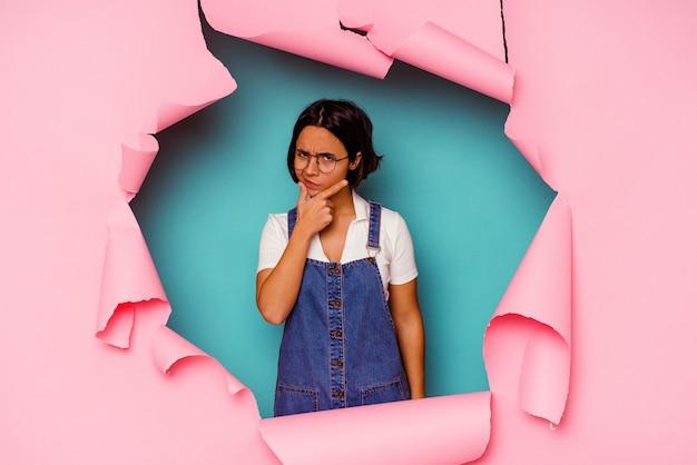 Jonge gemengde rasvrouw achter een gebroken achtergrond die naar verschillende exemplaarruimten wijst, een van hen kiest, met vinger toont.