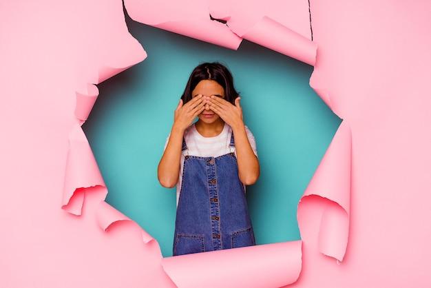Jonge gemengde rasvrouw achter een gebroken achtergrond met een sterke tandenpijn, kiespijn.