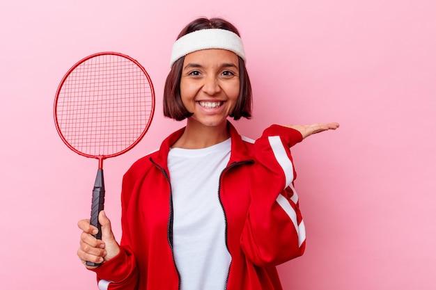 Jonge gemengde rasvrouw die badminton spelen dat op roze muur wordt geïsoleerd die een exemplaarruimte op een palm toont en een andere hand op taille houdt.