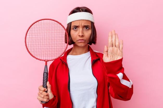 Jonge gemengde rasvrouw die badminton spelen dat op roze muur wordt geïsoleerd die zich met uitgestrekte hand bevindt die stopbord toont, dat u verhindert.