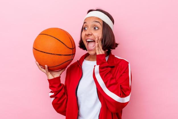 Jonge gemengde rasvrouw die basketbal spelen dat op roze muur wordt geïsoleerd die en palm dichtbij geopende mond houdt houdt.