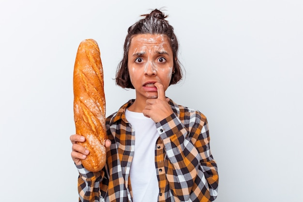 Jonge gemengde rasvrouw die brood maakt dat op witte achtergrond wordt geïsoleerd die vingernagels bijt, zenuwachtig en zeer angstig.