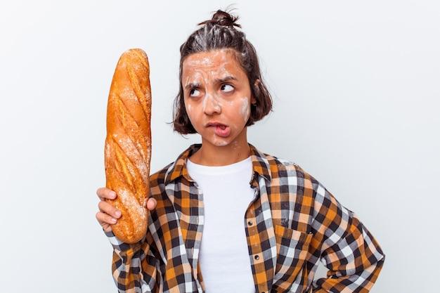 Jonge gemengde rasvrouw die brood maakt dat op witte muur verward wordt geïsoleerd, voelt twijfelachtig en onzeker.