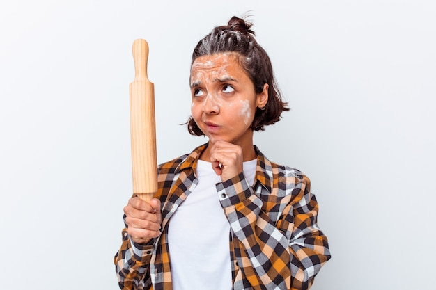 Jonge gemengde rasvrouw die brood maakt dat op witte muur wordt geïsoleerd die zijwaarts met twijfelachtige en sceptische uitdrukking kijkt.