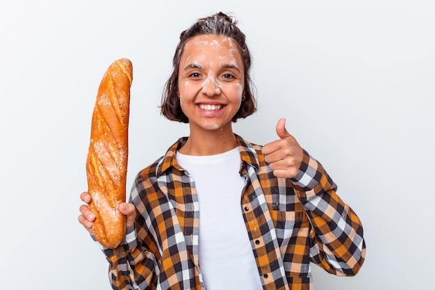Jonge gemengde rasvrouw die brood maken dat op witte muur wordt geïsoleerd die en duim glimlacht opheft