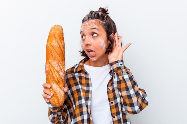 Jonge gemengde rasvrouw die brood maken dat op witte muur wordt geïsoleerd die probeert om een roddel te luisteren.