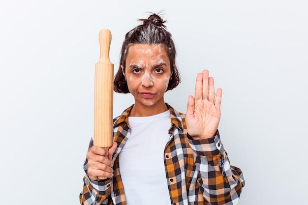 Jonge gemengde rasvrouw die brood maken dat op witte muur wordt geïsoleerd die zich met uitgestrekte hand bevindt die stopbord toont, dat u verhindert.