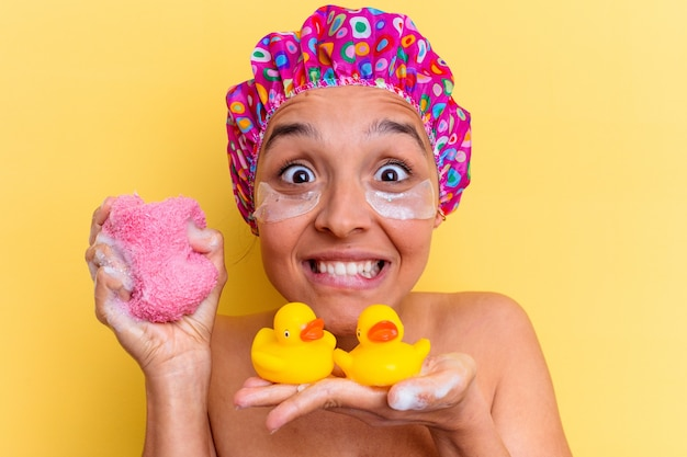 Jonge gemengde rasvrouw die een bad nemen met een spons en rubbereendjes