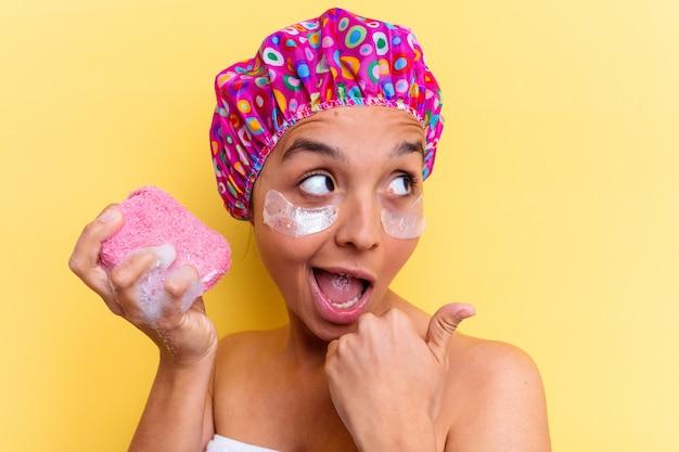 Jonge gemengde rasvrouw die een bad nemen met een spons met onderoogvlekken