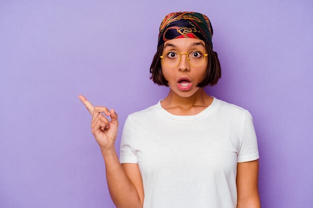 Jonge gemengde rasvrouw die een bandana draagt die op purpere achtergrond wordt geïsoleerd die naar de kant richt