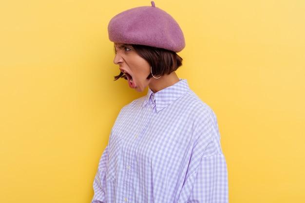 Jonge gemengde rasvrouw die een baret draagt die op gele achtergrond wordt geïsoleerd die naar een exemplaarruimte schreeuwt