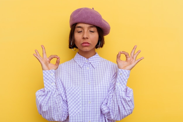 Jonge gemengde rasvrouw die een baret draagt die op gele achtergrond wordt geïsoleerd, ontspant na een zware werkdag, zij voert yoga uit.