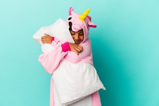 Jonge gemengde rasvrouw die een eenhoornpyjama draagt die een hoofdkussen houdt dat op blauwe achtergrond wordt geïsoleerd