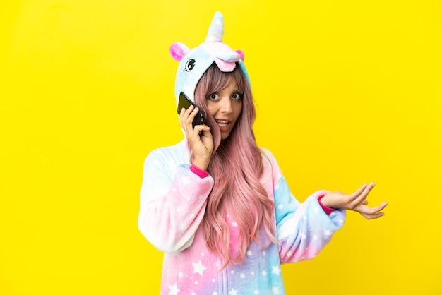 Jonge gemengde rasvrouw die een eenhoornpyjama draagt die op witte achtergrond wordt geïsoleerd en een gesprek met de mobiele telefoon met iemand houdt