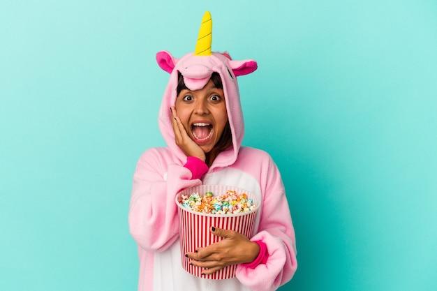 Jonge gemengde rasvrouw die een eenhoornpyjama draagt die popcorn eet