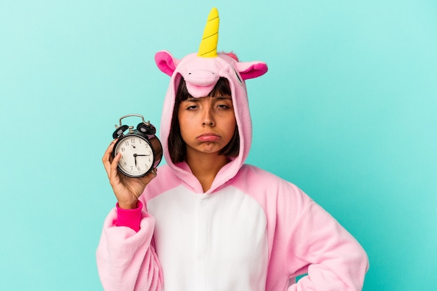 Jonge gemengde rasvrouw die een eenhoornpyjama draagt die wekker houdt die op blauwe achtergrond wordt geïsoleerd
