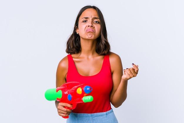 Jonge gemengde rasvrouw die een geïsoleerd waterpistool houden die tonen dat geen geld heeft.