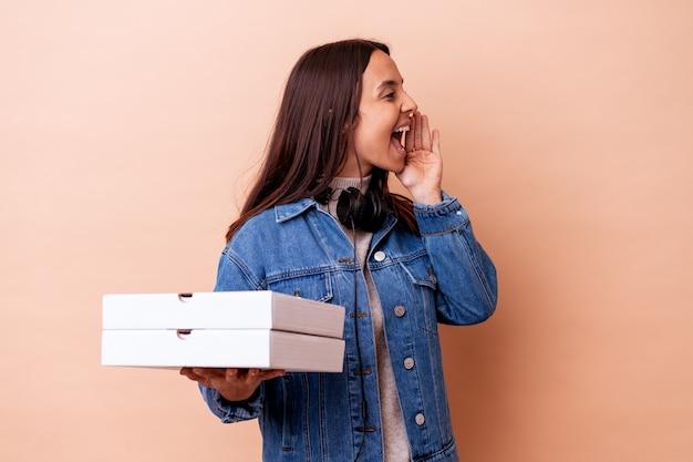 Jonge gemengde rasvrouw die een geïsoleerde pizza houden die en palm dichtbij geopende mond houdt.