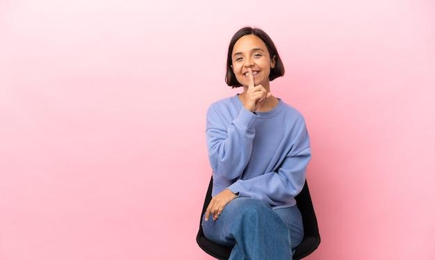 Jonge gemengde rasvrouw die een geïsoleerde stoel zit die een teken van stiltegebaar toont dat vinger in mond stopt