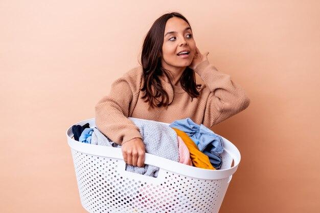 Jonge gemengde rasvrouw die een geïsoleerde wasserij houden die een roddel proberen te luisteren.