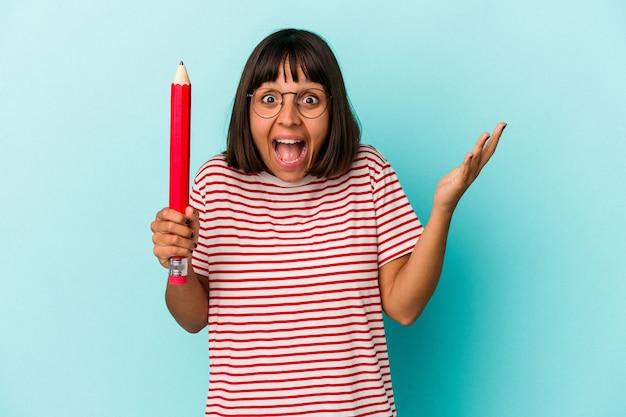 Jonge gemengde rasvrouw die een groot potlood houdt dat op blauwe achtergrond wordt geïsoleerd en een aangename verrassing ontvangt, opgewonden en handen opsteekt.