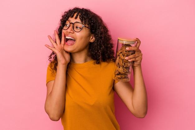 Jonge gemengde rasvrouw die een koekjeskruik houdt die op roze muur wordt geïsoleerd die en palm dichtbij geopende mond houdt houdt.