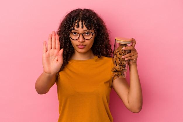 Jonge gemengde rasvrouw die een koekjespot houdt die op roze achtergrond wordt geïsoleerdd die zich met uitgestrekte hand toont die stopbord toont, die u verhinderen.