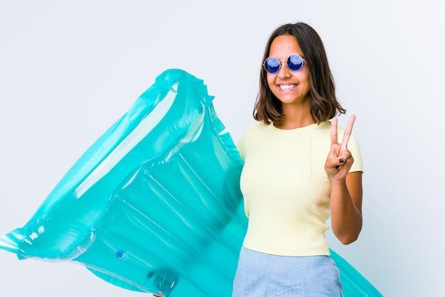 Jonge gemengde rasvrouw die een luchtmatras houdt die overwinningsteken toont en breed glimlacht.