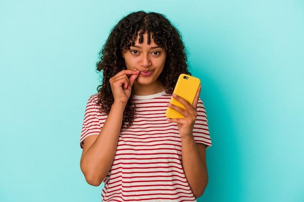 Jonge gemengde rasvrouw die een mobiele telefoon houdt die op blauwe achtergrond met vingers op lippen wordt geïsoleerd die een geheim houden.