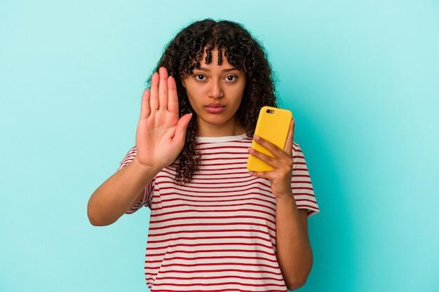 Jonge gemengde rasvrouw die een mobiele telefoon houdt die op blauwe achtergrond wordt geïsoleerd die zich met uitgestrekte hand bevindt die stopbord toont, die u verhinderen.