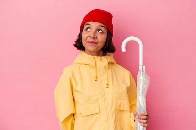 Jonge gemengde rasvrouw die een paraplu houden die op roze muur wordt geïsoleerd die van het bereiken van doelstellingen en doeleinden droomt