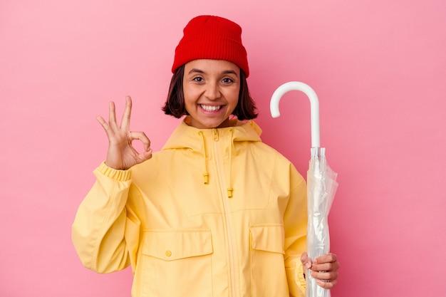 Jonge gemengde rasvrouw die een paraplu houden die op roze muur wordt geïsoleerd vrolijk en zelfverzekerd tonend ok gebaar