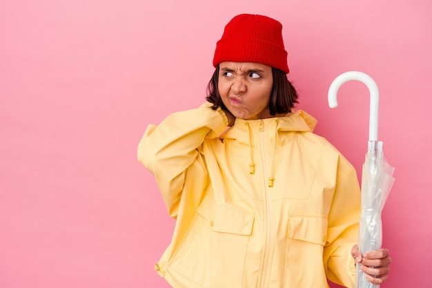 Jonge gemengde rasvrouw die een paraplu houdt die op roze muur wordt geïsoleerd die achterkant van het hoofd raakt, denkt en een keus maakt